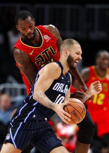 Orlando Magic guard Evan Fournier (10) is fouled by Atlanta Hawks center Dewayne Dedmon (14) during the first half of an NBA basketball game Sunday, Feb. 10, 2019, in Atlanta.