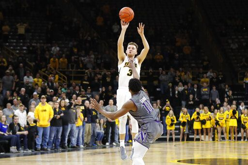 Iowa guard Jordan Bohannon (3) shoots a three point basket over Northwestern guard Anthony Gaines (11) at the end of an NCAA college basketball game, Sunday, Feb. 10, 2019, in Iowa City, Iowa. Iowa won 80-79.