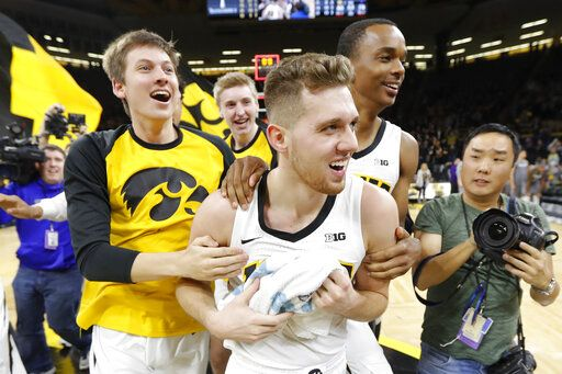 Iowa guard Jordan Bohannon, center, celebrates with teammates after an NCAA college basketball game against Northwestern, Sunday, Feb. 10, 2019, in Iowa City, Iowa. Bohannon made a three-point basket at the end of the game as Iowa won 80-79.