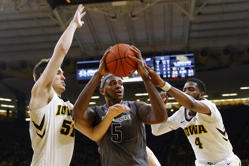 Northwestern center Dererk Pardon, center, grabs a rebound between Iowa's Nicholas Baer, left, and Isaiah Moss, right, during the first half of an NCAA college basketball game, Sunday, Feb. 10, 2019, in Iowa City, Iowa.