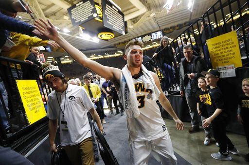 Iowa guard Jordan Bohannon celebrates with fans after an NCAA college basketball game against Northwestern, Sunday, Feb. 10, 2019, in Iowa City, Iowa. Bohannon made a three-point basket at the end of the game as Iowa won 80-79.