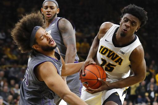Iowa forward Tyler Cook gets fouled by Northwestern center Barret Benson, left, while driving to the basket during the second half of an NCAA college basketball game, Sunday, Feb. 10, 2019, in Iowa City, Iowa. Iowa won 80-79.