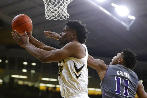 Iowa forward Tyler Cook, left, drives to the basket past Northwestern guard Anthony Gaines (11) during the second half of an NCAA college basketball game, Sunday, Feb. 10, 2019, in Iowa City, Iowa. Iowa won 80-79.