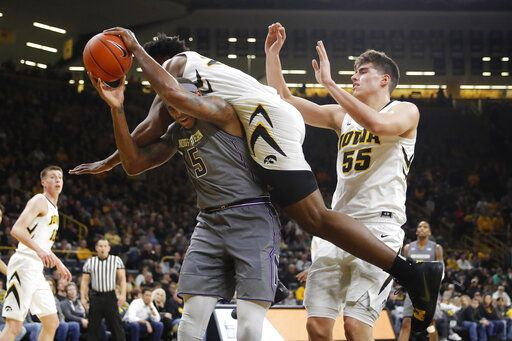 Northwestern center Dererk Pardon (5) is fouled by Iowa forward Tyler Cook while driving to the basket during the first half of an NCAA college basketball game, Sunday, Feb. 10, 2019, in Iowa City, Iowa. Iowa forward Luka Garza, right, looks on.