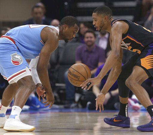 Phoenix Suns forward Mikal Bridges, right, steals the ball from Sacramento Kings forward Harrison Barnes during the first half of an NBA basketball game Sunday, Feb. 10, 2019, in Sacramento, Calif.