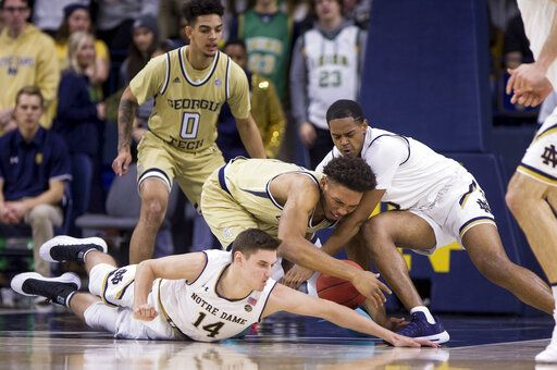 Notre Dame's Nate Laszewski (14) and D.J. Harvey, right, compete for a loose ball with Georgia Tech's James Banks III, center, during the first half of an NCAA college basketball game Sunday, Feb. 10, 2019, in South Bend, Ind.