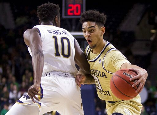 Georgia Tech's Michael Devoe (0) moves by Notre Dame's T.J. Gibbs Jr. (10) during the first half of an NCAA college basketball game Sunday, Feb. 10, 2019, in South Bend, Ind.