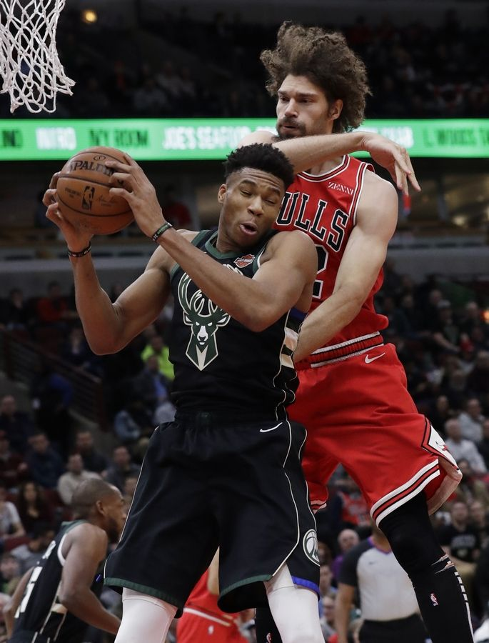 Milwaukee Bucks forward Giannis Antetokounmpo, left, rebounds a ball against Chicago Bulls center Robin Lopez during the first half of an NBA basketball game Monday, Feb. 11, 2019, in Chicago.