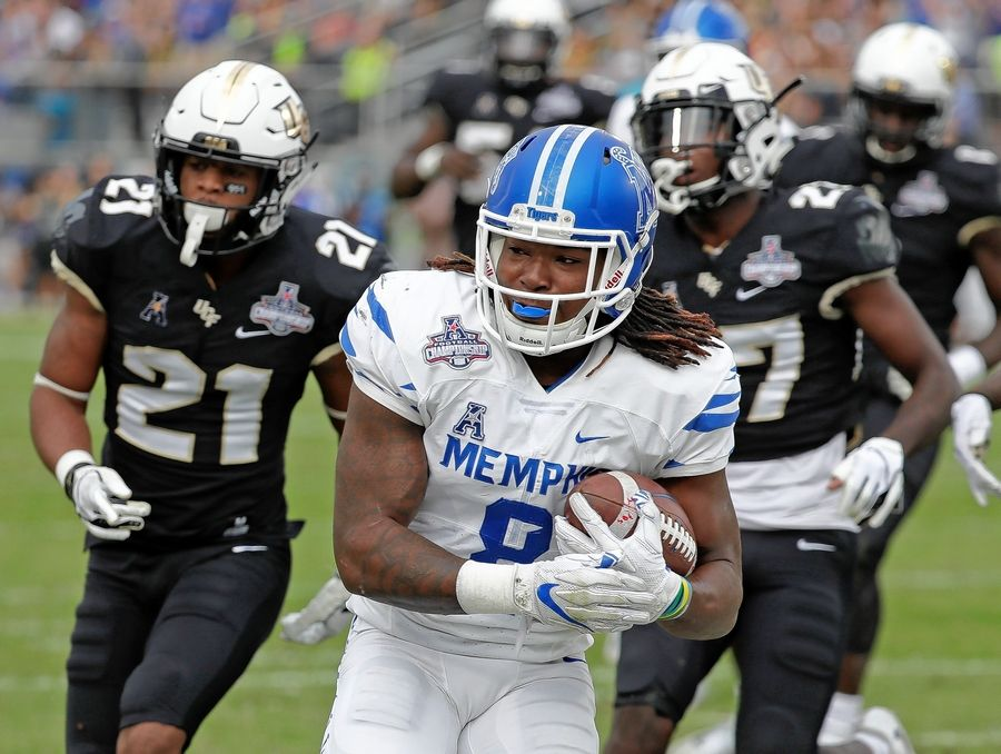 Memphis running back Darrell Henderson, center, runs past Central Florida defensive backs Rashard Causey (21) and  Richie Grant, right, for a 12-yard touchdown run during the first half of the American Athletic Conference championship NCAA college football game, Saturday, Dec. 1, 2018, in Orlando, Fla.