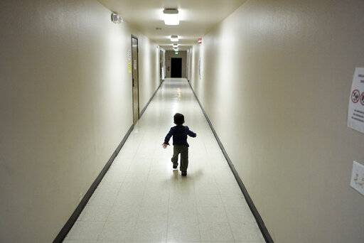 FILE - In this Dec. 11, 2018 file photo, an asylum-seeking boy from Central America runs down a hallway after arriving from an immigration detention center to a shelter in San Diego. Lawyers for eight immigrant families separated under Trump administration policy filed claims Monday, Feb. 11, 2019, against the U.S. government demanding $6 million each in damages for what they describe as lasting trauma.