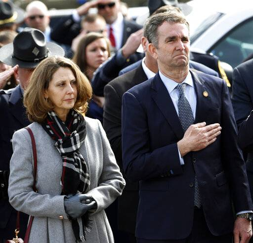 Virginia Gov. Ralph Northam, right, and his wife Pam, watch as the casket of fallen Virginia State Trooper Lucas B. Dowell is carried to a waiting tactical vehicle during the funeral at the Chilhowie Christian Church in Chilhowie, Va., Saturday, Feb. 9, 2019. Dowell was killed in the line of duty earlier in the week.
