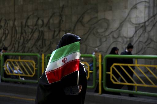 FILE - In this Feb. 11, 2016 file photograph, an Iranian woman holds the national flag during a rally commemorating the 37th anniversary of the Islamic revolution, in Tehran, Iran. Iran's 1979 Islamic Revolution initially inspired both Islamic militants and Islamists across the Mideast. They saw the revolution as the starting gun in a competition to push out the strongman Arab nationalism that had taken hold across the Middle East. However, analysts say Iran's push to back militants in the wider Mideast and Saudi Arabia's efforts to mobilize the Sunni world against the Shiite power would turn many away.