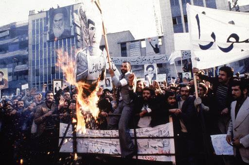 FILE - In an undated photo from 1979, protestors burn an effigy of Shah Mohammad Reza Pahlavi during a demonstration in front of the U.S. Embassy in Tehran, Iran. Forty years ago, Iran's ruling shah left his nation for the last time and an Islamic Revolution overthrew the vestiges of his caretaker government. The effects of the 1979 revolution, including the takeover of the U.S. Embassy in Tehran and ensuing hostage crisis, reverberate through decades of tense relations between Iran and America.