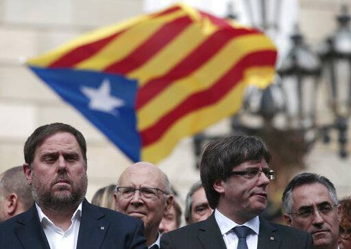 FILE - In this Monday, Oct. 2, 2017 file photo, Catalan regional Vice-President, Oriol Junqueras, left, and Catalan President, Carles Puigdemont, attend a protest called by pro-independence supporters outside the Palau Generalitat in Barcelona, Spain. Spain's Supreme Court is bracing to hold the nation's most sensitive trial in four decades of democracy this week with all eyes focused on its ability to stand up to concerted campaign by Catalonia's separatists to attack its credibility. Twelve high-profile Catalan separatists will face charges including rebellion for their role in a failed attempt to achieve secession for the prosperous north-eastern region in 2017.