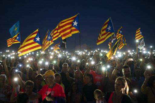 "FILE - In this Sunday, Sept. 30, 2018 file photo, pro-independence demonstrators wave ""esteladas"" or independence flags, as they sing in a field overlooking the Lledoners prison in Sant Joan de Vilatorrada, about 50 kilometres away from Barcelona, Spain. Spain's Supreme Court is bracing to hold the nation's most sensitive trial in four decades of democracy this week with all eyes focused on its ability to stand up to concerted campaign by Catalonia's separatists to attack its credibility."