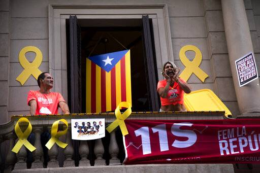 FILE - In this Tuesday, Sept. 11, 2018 file photo, a woman shouts slogans from her balcony during the Catalan National Day in Barcelona, Spain. Spain's Supreme Court is bracing to hold the nation's most sensitive trial in four decades of democracy this week with all eyes focused on its ability to stand up to concerted campaign by Catalonia's separatists to attack its credibility.