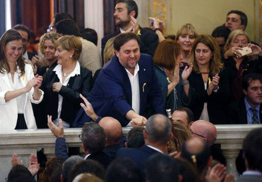 FILE - In this Friday, Oct. 27, 2017 file photo, Catalan Vice President Oriol Junqueras, center, is greeted after a vote on independence in the Catalan parliament in Barcelona, Spain. Spain's Supreme Court is bracing to hold the nation's most sensitive trial in four decades of democracy this week with all eyes focused on its ability to stand up to concerted campaign by Catalonia's separatists to attack its credibility. Twelve high-profile Catalan separatists will face charges including rebellion for their role in a failed attempt to achieve secession for the prosperous north-eastern region in 2017.