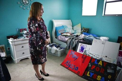 "Lori Alhadeff, mother of 14-year-old Alyssa Alhadeff who was one of 17 people killed at Marjory Stoneman Douglas High School, stands in her daughter's bedroom on Wednesday, Jan. 30, 2019, in Parkland, Fla. Much of the teenager's turquoise-colored bedroom remains untouched. Her retainer is still there, as are mementos of teammates and friends. And her dirty clothes are still in the hamper by the bed. ""I haven't washed them yet because it's too hard,"" her mother says, crying again."