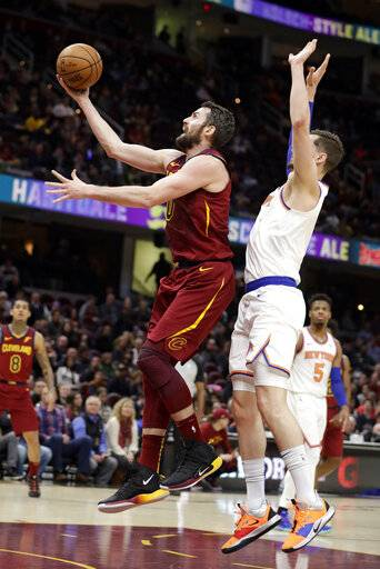 Cleveland Cavaliers' Kevin Love, left, drives to the basket against New York Knicks' Mario Hezonja, from Croatia, in the first half of an NBA basketball game, Monday, Feb. 11, 2019, in Cleveland.
