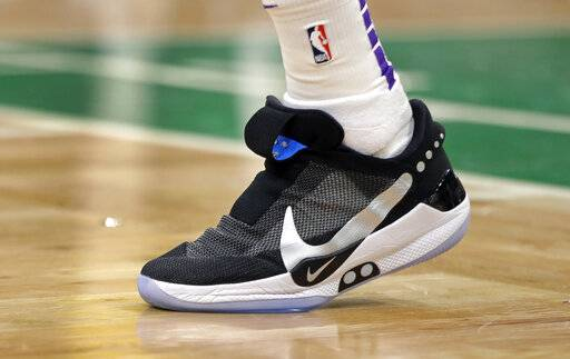 In this Feb. 7, 2019, photo, Los Angeles Lakers forward Kyle Kuzma walks on the court during an NBA basketball game against the Boston Celtics in Boston. He is wearing Nike's latest performance basketball shoes, which from concept to reality, took about three years to put together. Or 30 years, depending on how you count. The Nike Adapt BB _ a self-lacing smart shoe that can be controlled by a smartphone _ gets released to the public on Sunday, Feb. 17, 2019, a date that just happens to coincide with the NBA All-Star Game in Charlotte. It has a motor embedded within the shoe, and a hefty $350 price tag. It has a motor embedded within the shoe, and a hefty $350 price tag.