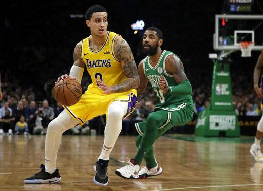 In this Feb. 7, 2019 photo, Los Angeles Lakers forward Kyle Kuzma (0) drives against Boston Celtics guard Kyrie Irving during an NBA basketball game in Boston. Kuzma is wearing Nike's latest performance basketball shoes, which from concept to reality, took about three years to put together. Or 30 years, depending on how you count. The Nike Adapt BB _ a self-lacing smart shoe that can be controlled by a smartphone _ gets released to the public on Sunday, Feb. 17, 2019, a date that just happens to coincide with the NBA All-Star Game in Charlotte. It has a motor embedded within the shoe, and a hefty $350 price tag. It has a motor embedded within the shoe, and a hefty $350 price tag.