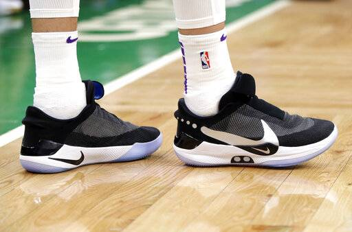 In this Feb. 7, 2019, photo, Los Angeles Lakers forward Kyle Kuzma stands on the court during an NBA basketball game against the Boston Celtics in Boston. He is wearing Nike's latest performance basketball shoes, which from concept to reality, took about three years to put together. Or 30 years, depending on how you count. The Nike Adapt BB _ a self-lacing smart shoe that can be controlled by a smartphone _ gets released to the public on Sunday, Feb. 17, 2019, a date that just happens to coincide with the NBA All-Star Game in Charlotte. It has a motor embedded within the shoe, and a hefty $350 price tag.