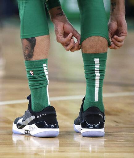 In this Feb. 7, 2019, photo, Boston Celtics forward Jayson Tatum adjusts his knee sleeve during an NBA basketball game against the Los Angeles Lakers in Boston. He is wearing Nike's latest performance basketball shoes, which from concept to reality, took about three years to put together. Or 30 years, depending on how you count. The Nike Adapt BB _ a self-lacing smart shoe that can be controlled by a smartphone _ gets released to the public on Sunday, Feb. 17, 2019, a date that just happens to coincide with the NBA All-Star Game in Charlotte. It has a motor embedded within the shoe, and a hefty $350 price tag.