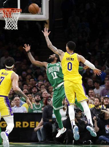 In this Feb. 7, 2019, photo, Los Angeles Lakers forward Kyle Kuzma (0) defends against Boston Celtics guard Kyrie Irving (11) during an NBA basketball game in Boston. Kuzma is wearing Nike's latest performance basketball shoes, which from concept to reality, took about three years to put together. Or 30 years, depending on how you count. The Nike Adapt BB _ a self-lacing smart shoe that can be controlled by a smartphone _ gets released to the public on Sunday, Feb. 17, 2019, a date that just happens to coincide with the NBA All-Star Game in Charlotte. It has a motor embedded within the shoe, and a hefty $350 price tag. It has a motor embedded within the shoe, and a hefty $350 price tag.