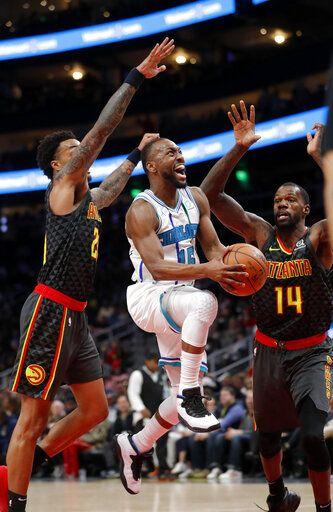 0cd69d73ed51 Charlotte Hornets guard Kemba Walker (15) goes between Atlanta Hawks  John  Collins (