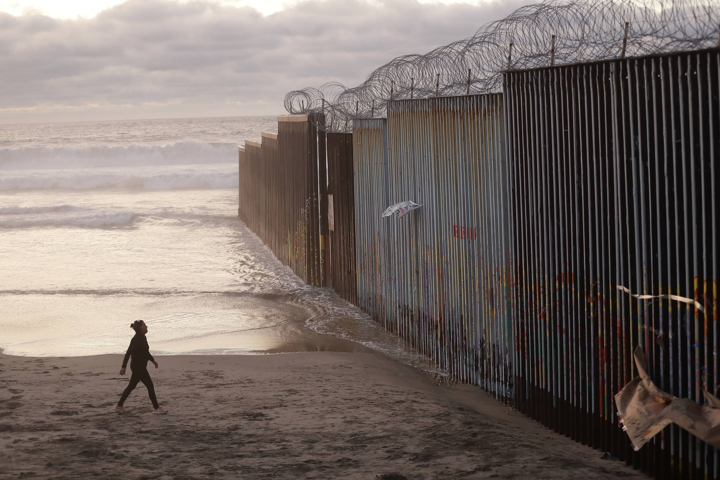 In this Jan. 9 photo, a woman next to the border wall topped with razor wire in Tijuana, Mexico. Congressional negotiators reached a deal to prevent a government shutdown and to construct new barriers on the southern border.