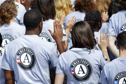 FILE- In this Sept. 12, 2014 file photo, as President Barack Obama and former President Bill Clinton mark the 20th anniversary of the AmeriCorps national service program, hundreds of new volunteers are sworn in for duty at a ceremony on the South Lawn of the White House in Washington. Hundreds of Teach for America alumni are slamming the educator placement program for telling members to cross the picket line during a potential teacher strike in Oakland, California, or risk losing thousands of dollars at the end of their service. In partnership with the AmeriCorps, Teach for America members can apply for an education award at the end of their service to help pay off student loans. An AmeriCorps spokeswoman couldn't immediately provide comment but said striking is prohibited.