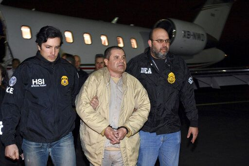 "FILE - In this Jan. 19, 2017 file photo provided U.S. law enforcement, authorities escort Joaquin ""El Chapo"" Guzman, center, from a plane to a waiting caravan of SUVs at Long Island MacArthur Airport, in Ronkonkoma, N.Y. The Sinaloa cartel marches on following the conviction in New York of kingpin Joaquin ""El Chapo� Guzman on Tuesday, Feb. 12, 2019.  (U.S. law enforcement via AP, File)"