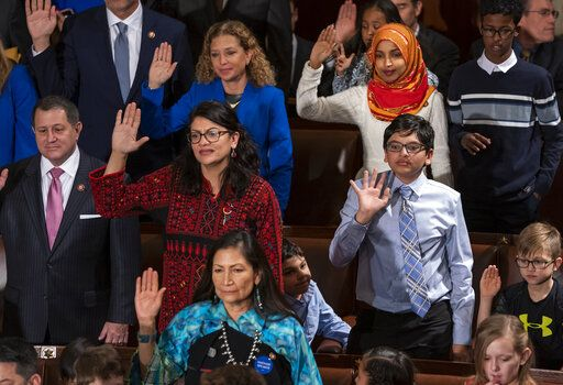 FILE - In this Jan. 3, 2019 file photo, Rep. Rashida Tlaib, D-Mich., center left, wears a Palestinian thobe as Democratic members of the House of Representatives take their oath on the opening day of the 116th Congress, at the Capitol in Washington. Tlaib proudly wore her thobe to her historic swearing-in as the first Palestinian American member of Congress, inspiring women around the world to tweet photos of themselves in their ancestral robes.