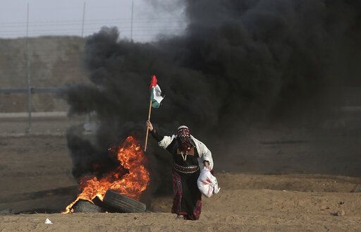 FILE - In this Oct. 5, 2018 file photo, a Palestinian woman wearing a traditional thobe, carries a Palestinian flag during a protest at the Gaza Strip's border with Israel. The thobe, a brightly embroidered robe for women, has long been a staple of Palestinian life, sewn by village women and worn at weddings and parties. Now it's gaining prominence as a softer symbol of Palestinian nationalism, competing with the classic keffiyeh. Rashida Tlaib proudly wore her thobe to her historic swearing-in as the first Palestinian American member of Congress, inspiring women around the world to tweet photos of themselves in their ancestral robes.