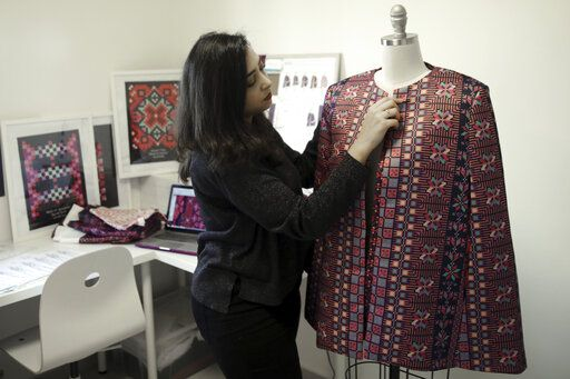 "In this Tuesday, Jan. 29, 2019 photo, designer Natalie Tahhan works on a modern version of the traditional Palestinian thobe in her studio in east Jerusalem. Tahhan, a designer based in east Jerusalem, produces capes from digital prints that replicate traditional embroidery stitches, ""connecting tradition with what is new and stylish.� The thobe has long been a staple of Palestinian life, sewn by village women and worn at weddings and parties."