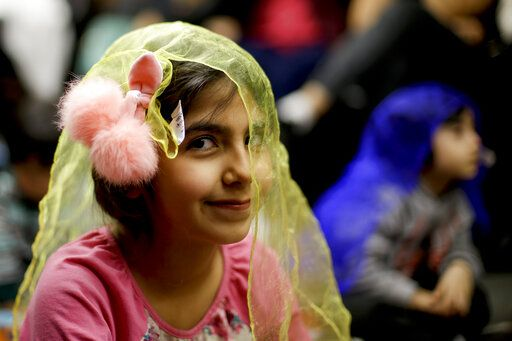 In this Wednesday, Jan. 23, 2019, photo, Melorin Issarezal 8, plays with a scarf during Persian story time at Irvine public library in Irvine, Calif. It's been four decades since the Iranian revolution overthrew the ruling shah, prompting tens of thousands of Iranian exiles and refugees to make their lives in the United States. Years later, they have set down roots here and are finding ways to pass their love of Iranian culture to their American children and grandchildren.