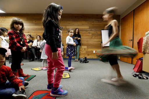 In this Wednesday, Jan. 23, 2019 photo, children dance during Persian story time at Irvine public library in Irvine, Calif. It's been four decades since the Iranian revolution overthrew the ruling shah, prompting tens of thousands of Iranian exiles and refugees to make their lives in the United States. Years later, they have set down roots here and are finding ways to pass their love of Iranian culture to their American children and grandchildren.