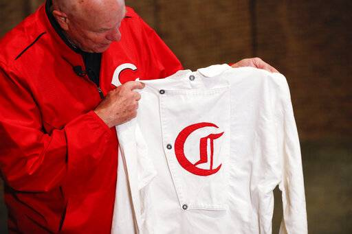 "Greg Rhodes, the Cincinnati Reds baseball team historian, holds a replica jersey of the early Cincinnati Red Stockings team at Cincinnati Reds Hall of Fame, Tuesday, Jan. 8, 2019, in Cincinnati. The Reds will play games in 15 sets of throwback uniforms, including navy blue and a ""Palm Beach"" style, during a season-long celebration of the 1869 Red Stockings who pioneered professional baseball."