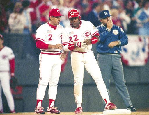 FILE - In this Oct. 17, 1990 file photo, Cincinnati Reds Billy Hatcher (22) confers with third base coach Sam Perlozzo (2) after Hatchers triple in the eighth inning against the Oakland Athletics in the second game of the World Series in Cincinnati.
