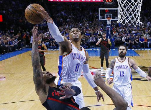 Oklahoma City Thunder guard Russell Westbrook (0) blocks a shot by Portland Trail Blazers guard Damian Lillard, left, in the first half of an NBA basketball game in Oklahoma City, Monday, Feb. 11, 2019.