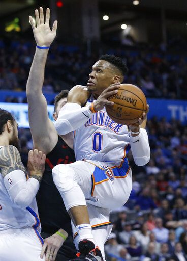 Oklahoma City Thunder guard Russell Westbrook, right, goes to the basket past Portland Trail Blazers center Jusuf Nurkic, center, in the first half of an NBA basketball game in Oklahoma City, Monday, Feb. 11, 2019.