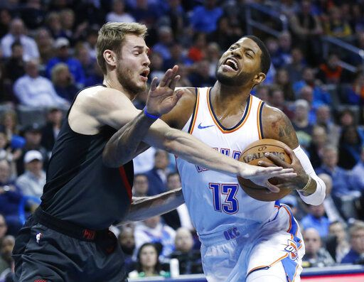 Oklahoma City Thunder forward Paul George (13) is fouled by Portland Trail Blazers forward Jake Layman, left, as he drives to the basket in the first half of an NBA basketball game in Oklahoma City, Monday, Feb. 11, 2019.
