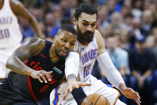 Portland Trail Blazers guard Damian Lillard (0) and Oklahoma City Thunder center Steven Adams (12) reach for the ball in the first half of an NBA basketball game in Oklahoma City, Monday, Feb. 11, 2019.
