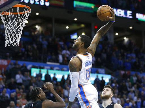 Oklahoma City Thunder forward Paul George (13) goes up for a dunk between Portland Trail Blazers forward Al-Farouq Aminu, left, and center Jusuf Nurkic, right, in the first half of an NBA basketball game in Oklahoma City, Monday, Feb. 11, 2019.