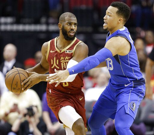 Houston Rockets guard Chris Paul, left, looks to pass as Dallas Mavericks guard Jalen Brunson applies defensive pressure during the first half of an NBA basketball game, Monday, Feb. 11, 2019, in Houston.