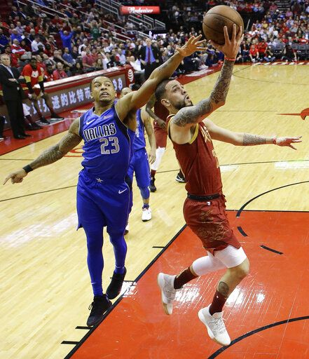 Houston Rockets guard Austin Rivers, right, drives to the basket as Dallas Mavericks guard Trey Burke defends during the first half of an NBA basketball game, Monday, Feb. 11, 2019, in Houston.