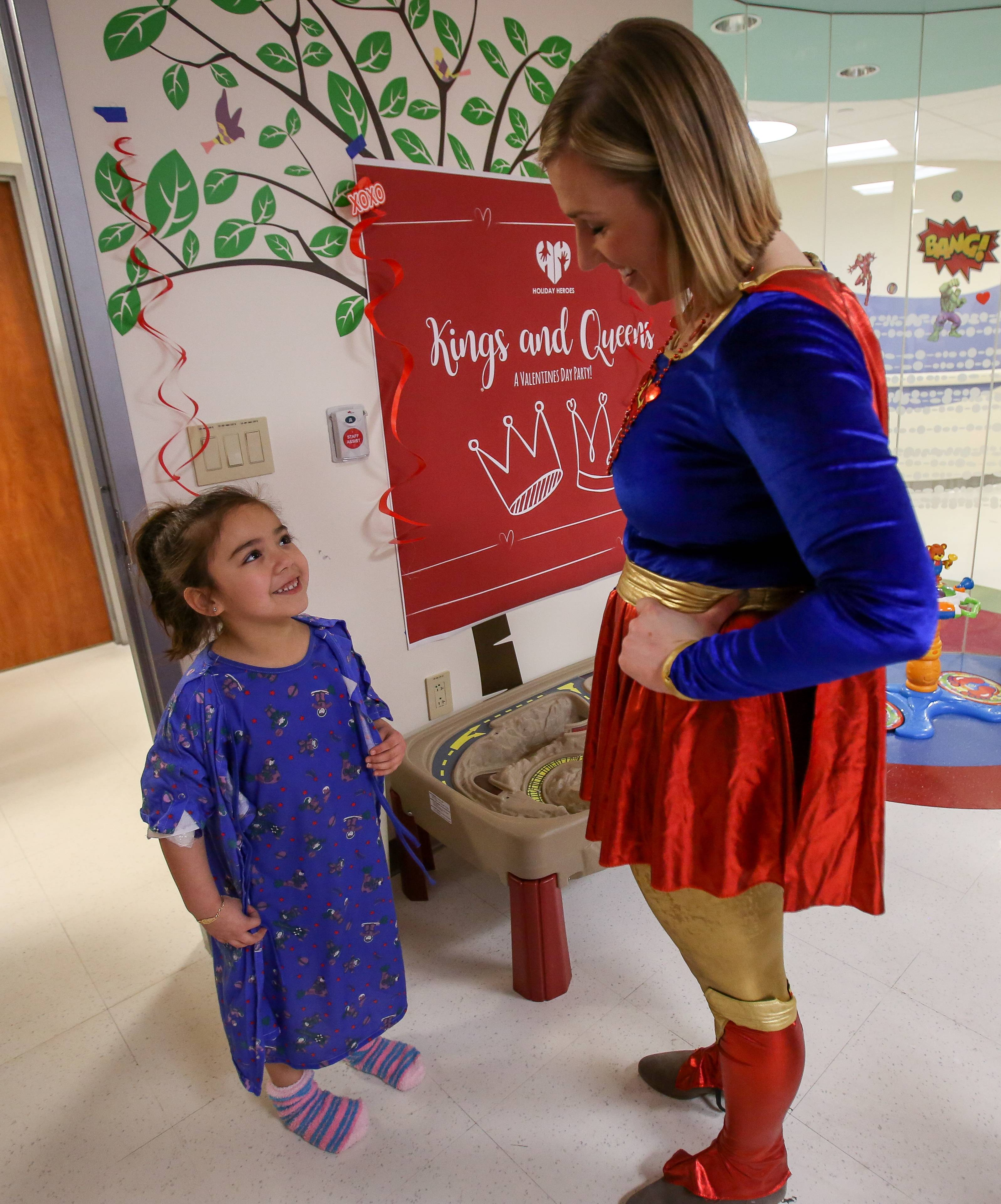 Camila Acosta, 5, of Aurora meets Supergirl during the hero's visit to deliver valentines to pediatric patients Thursday at Northwestern Medicine Central DuPage Hospital in Winfield. Supergirl was portrayed by Morgan Olenski, an associate board member with Holiday Heroes.