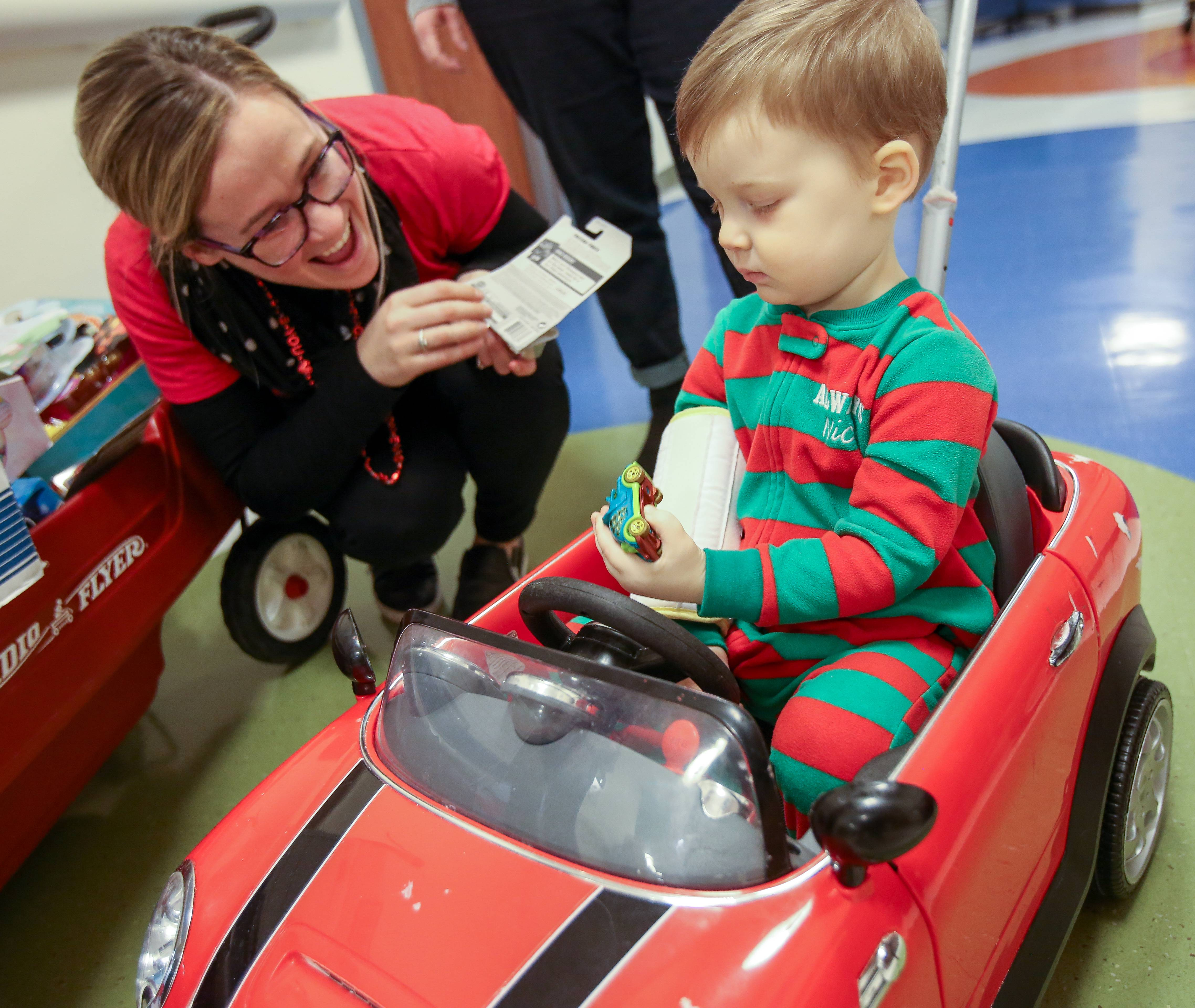 Maggie Drain, development and program coordinator for Holiday Heroes, gives some toy cars to Logan Klemencic, 23 months, of Sugar Grove for Valentine's Day on Thursday at Northwestern Medicine Central DuPage Hospital in Winfield.