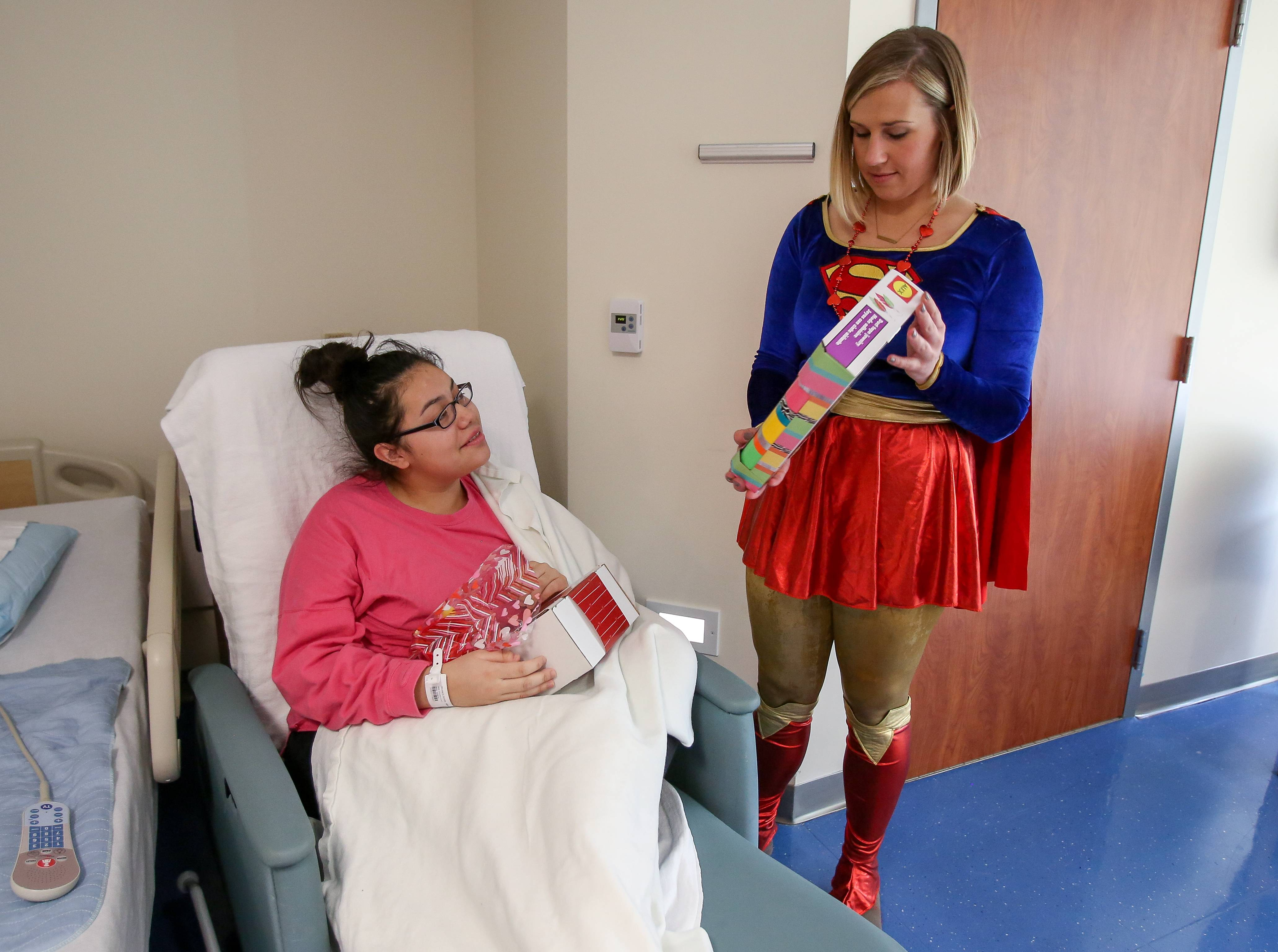 Supergirl, played by Morgan Olenski, delivers a Valentine's Day present to Alondra Alvarado, 15, of Addison on Thursday at Northwestern Medicine Central DuPage Hospital in Winfield