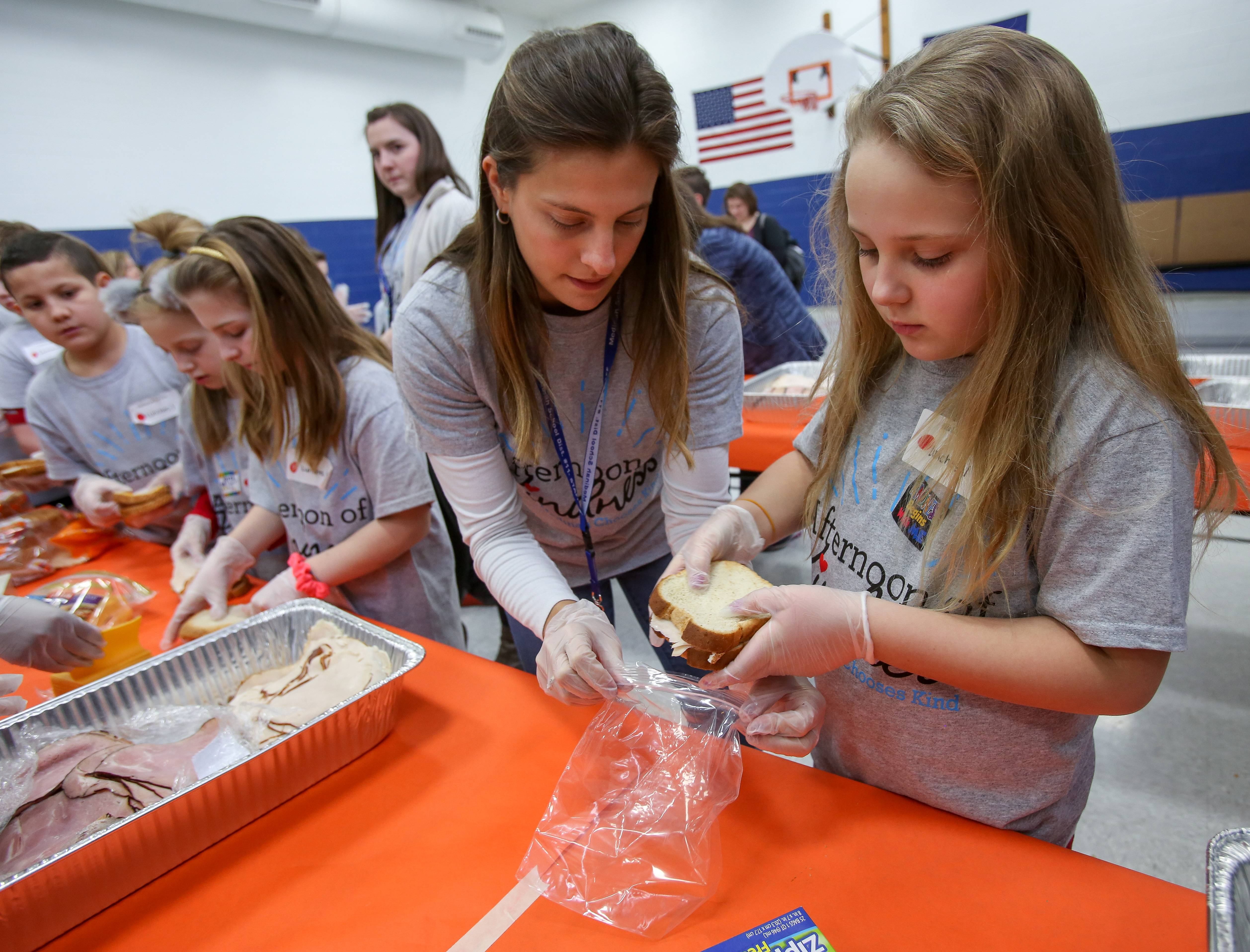 Medinah Intermediate School fourth-grade teacher Lindsay Parker helps third-grade student Julia Ziemkiewicz pack a sandwich Thursday for a lunch to donate to the homeless services agency DuPage Pads. The assembly of lunches was one of five service projects during the first schoolwide Afternoon of Kindness to celebrate Valentine's Day.
